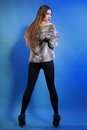 Young woman in fur long hair blue background full length fashionable coat back view Royalty Free Stock Photo