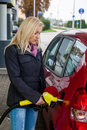 A young woman at a gas station gasoline tank the cost of the car because of the gas prices are getting more expensive Royalty Free Stock Photos