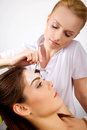 Young woman getting beauty skin mask treatment on her face with women brush Royalty Free Stock Images