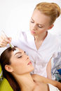 Young woman getting beauty skin mask treatment on her face with women brush Stock Photo
