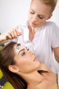 Young woman getting beauty skin mask treatment on her face with women brush Stock Photography