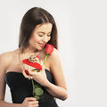 Young woman with a gift and a flower holding rose Royalty Free Stock Image