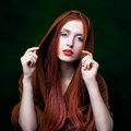Young woman with ginger hair and scarf on green background Royalty Free Stock Photo