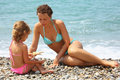 Young woman with girl played starfish on beach Royalty Free Stock Photo