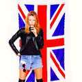 Young woman with glass of alcohol standing over the union jack flag overthe on white background not isolated Royalty Free Stock Images