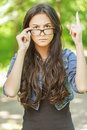 Young woman glasses frown beautiful long dark hair wearing severe points finger up Royalty Free Stock Photo