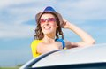 Young woman got out of car window the holds the hand hat and laughing Stock Images