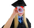 Young woman in graduation gown looking through diploma Royalty Free Stock Images