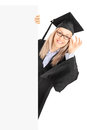 Young woman in graduation gown standing behind blank panel Stock Photo