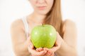 A young woman with a green apple on bright background Stock Image