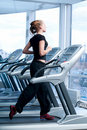 Young woman at the gym. Run on a machine Royalty Free Stock Photo