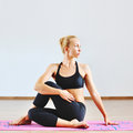 Young woman in half spinal twist pose Royalty Free Stock Photo