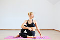 Young woman in half spinal twist pose on mat Royalty Free Stock Photo