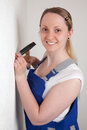 Young woman with hammer and nail drives a into the wall a Stock Images