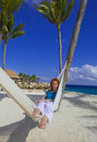 Young woman in hammock on background of palm trees Stock Photos