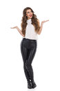 Young woman with hands raised smiling in white shirt leather trousers and boots holding and looking away full length studio shot Stock Photos