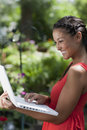 Young Woman Happily Working on a Laptop Outdoors Stock Photography