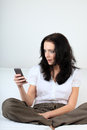 Young woman with happy expression looking at message on her cell phone Royalty Free Stock Photo