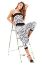 Young woman in harem pants posing with step ladder on white Royalty Free Stock Photography