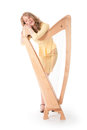 Young woman and harp in sexy yellow mini dress standing behind Stock Image