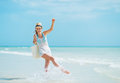 Young woman with hat and bag having fun time at seaside white Stock Photography