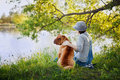 Young woman in a hat with dog Shar Pei sitting in the field and looking to the river in golden sunset light