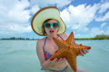 Young woman in hat posing with sea star on background Royalty Free Stock Image