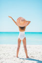 Young woman in hat rejoicing on beach rear view white swimsuit and Royalty Free Stock Images