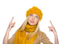 Young woman in hat and scarf pointing up on copy space high resolution photo Stock Photos