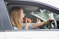 Young woman having coffee and doughnut in her car Royalty Free Stock Photography