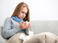 Young woman having a cold sick covered with blanket holding cup of tea sitting on sofa couch Stock Images