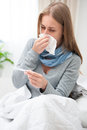 Young woman having a cold sick with thermometer in bed flu fever and migraine Royalty Free Stock Photography