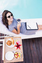 Young woman having cup of tea near poolside portrait and relaxing on a sun lounger Stock Photos