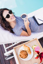 Young woman having cup of tea near poolside portrait and relaxing on a sun lounger Royalty Free Stock Photo