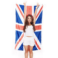 Young woman having fun next the union jack flag girl standing on white background not isolated Stock Image
