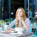 Young woman having healthy breakfast in outdoor cafe Royalty Free Stock Photo