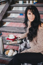 Young woman having picnic drinking tea and reading book on wooden stairs Stock Photo
