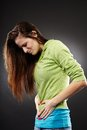 Young woman having a severe abdominal pain studio shot of over grey background Royalty Free Stock Photo