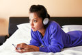 Young woman in headphones listening to the music in bed a blue top and Royalty Free Stock Images
