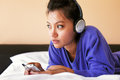 Young woman in headphones listening to the music in bed a blue top and Royalty Free Stock Photography