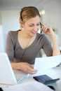 Young woman with headset working at home from laptop and Royalty Free Stock Images
