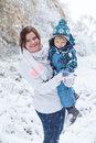 Young woman and her little son having fun with snow in winter fo women forest Royalty Free Stock Photography