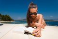 Young woman on her private yacht in bikini reading a book Stock Photo