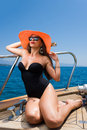 Young woman on her private yacht with orange straw hat Stock Photos