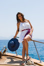 Young woman on her private yacht with white shirt and straw hat Royalty Free Stock Photos