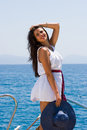 Young woman on her private yacht with white shirt and straw hat Stock Photography