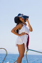 Young woman on her private yacht with white shirt and straw hat Royalty Free Stock Images