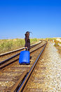 Young woman with her suitcase on a railroad track traveler Royalty Free Stock Photo