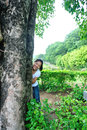 Young woman hide smile behind lime tree park Royalty Free Stock Images