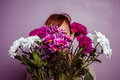 Young woman hiding behind a bouquet of flowers is Stock Photo